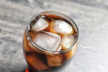 Glass of refreshing cola with ice on table