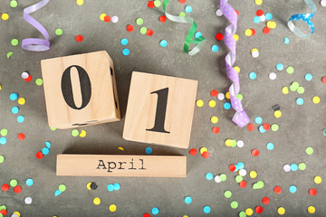 Composition with block calendar and confetti on grey background. April fool's day celebration