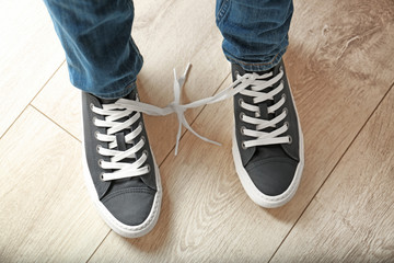 Man with shoelaces tied together. April fool's day prank Wall mural