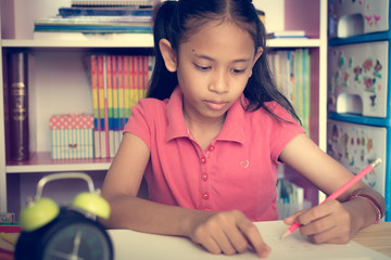 Little girl drawing on table at home.