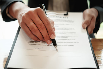 Real estate agent with hand putting signing contract,have a contract in place to protect it,signing of modest agreements form in office.Concept real estate,moving home or renting property