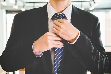 Asian young businessman in black suit Adjust Necktie his Suit