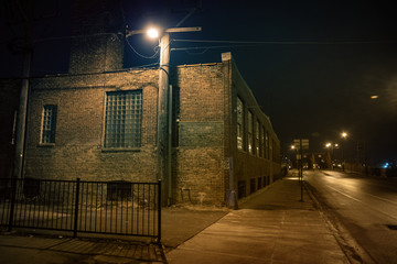 Fotomurales - Dark urban city street and alleyway corner with an industrial warehouse factory and an urban road leading to a vintage bridge in Chicago at night.