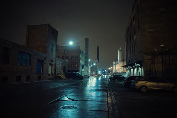 Foggy industrial urban street city night scenery in Chicago with vintage warehouses, factories and smokestacks after a rain.