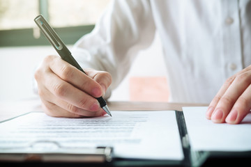 Close up business man reaching out sheet with contract agreement proposing to sign.Full and accurate details, individual who owns the business sign personally,director of the company, solicitor.
