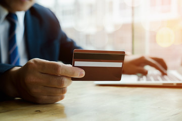asian young business man hands holding credit card and using laptop smart phone Online shopping.Online shopping concept