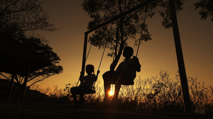 Silhouetted children boy and girl enjoying beautiful sunny day playing on swing set. Red orange sunset background.