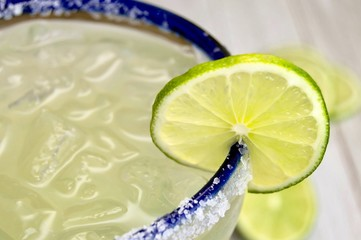 Close up of a salted, blue rimmed margarita glass with lime slice