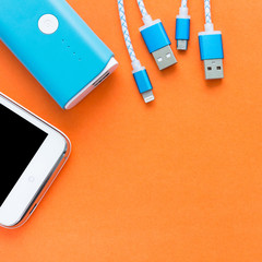 USB charging cables for smartphone and tablet in top view on orange background