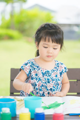 Little asian girl painting at park outdoor in school.