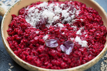 Close-up of risotto with beetroot and parmesan, selective focus, studio shot