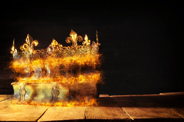 low key of queen/king crown burning over old books. vintage filtered. fantasy medieval period.