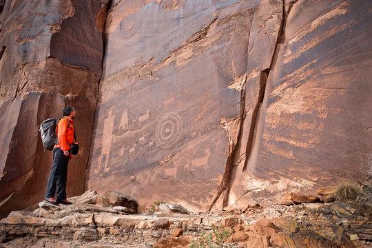 Man looking at rock art of Pueblo Indians. Owl, thunderbird, goat and a man figure petroglyphs on sandstone wall near Moab in Utah. Moab. Utah. United States. – Version 2