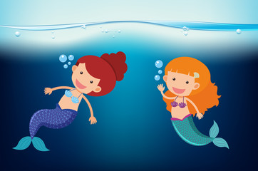 Two mermaids swimming under the sea