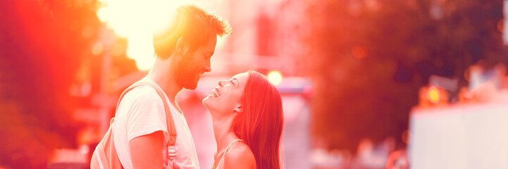 Couple falling in love dating laughing having fun on summer outdoor date in sunset. Panorama...