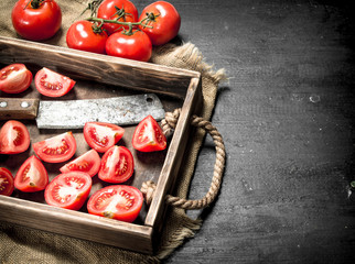 Tomatoes with old hatchet on the tray.