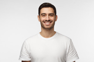 Close up portrait of smiling handsome man in white t-shirt looking at camera, isolated on gray background