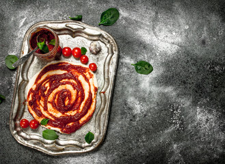 Roll up dough with tomato sauce and various ingredients.