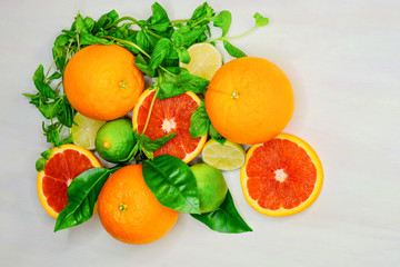 Fresh juicy citrus fruits and mint leafs background include blood orange, orange, lime and lime leaf on the white table