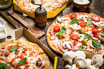 variety of pizzas with mushrooms and sauce.