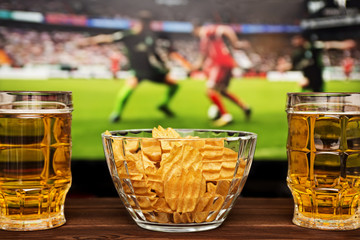 Two glass of cold beer and chips, football match in background