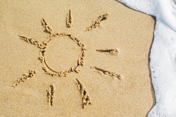 Sun drawing drawn on a beach on the golden sand background with sea wave and foam on summer vacation at the resort