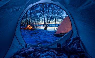 Camp by the lake with campfire at dusk in winter