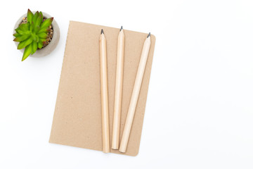Three pencils and notebook of kraft paper on a white background.  Scandinavian style.