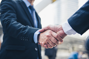Business people shaking hands, Greeting Deal Concept, modern city background.