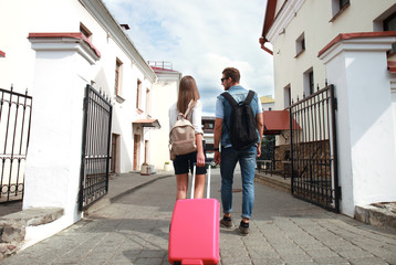 Two travelers on vacation walking around the city with luggage.