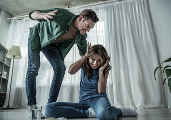 Low angle of irritated husband beating his wife with aggression. Fearful woman is sitting on floor near pills. Family violence concept