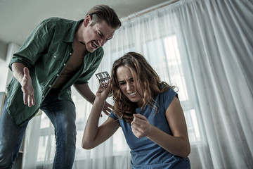 What did you do. Low angle of angry man shouting at his wife while woman is showing empty pack of pills to him. Suicide concept