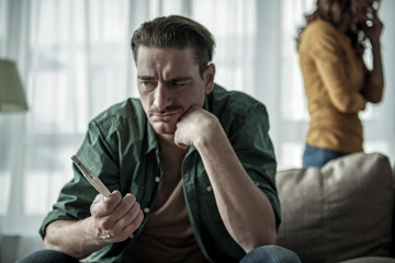 Sad couple finding out female pregnant state. Focus on pregnancy test stick with two strips in male hand
