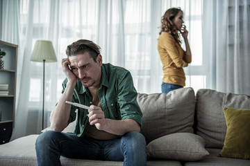 Worried man is holding pregnant test stick with frustration. He is sitting on sofa while nervous woman standing new window on background