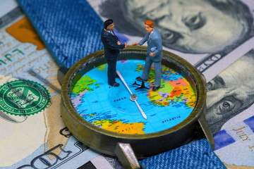 Two businessman figurines on time and money background. Worldwide business concept.