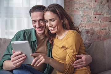 Waist up portrait of happy married couple using tablet with excitement. They are cuddling and smiling. Home relaxation concept