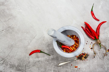 Hot red pepper flakes in a marble mortar and peppercorns on stone table