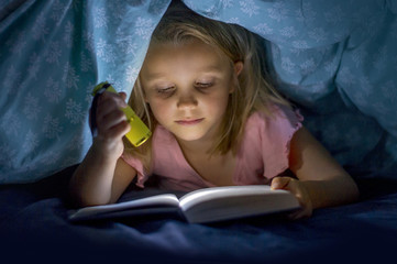 sweet beautiful and pretty little blond girl 6 to 8 years old under bed covers reading book in the dark at night with torch light smiling happy