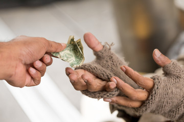 Man's holdind money gives money to a homeless person. Senior person hands begging for money