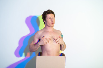 Portrait of cheerful young male with naked torso covering nipples. Delivery and fun concept