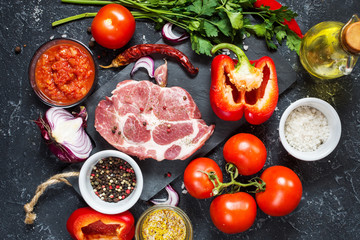 Raw marbled meat steak with ingredients for cooking on dark stone background.