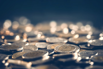 Close up money coin on the floor in dark light , business and financial for a money saving or investment background concept with black copy space , extremely close up and shallow DOF