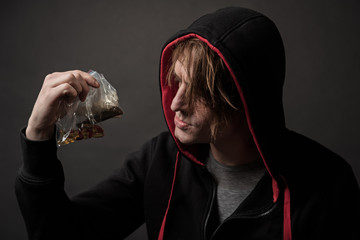 Troubled freak holding little bags with various drugs inside. He is examining them with attention. Isolated on background