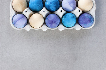 Background with blue and violet easter eggs in the box on the textured gray table