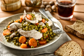 boiled chicken with a side of peas and carrots