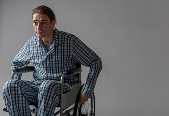 Portrait of tranquil disabled man carrying himself in armchair. Copy space in right side. Isolated on background