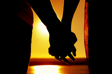 Close-up - silhouettes of hands holding each other against the background of sea in  sunset at the quiet sunny evening