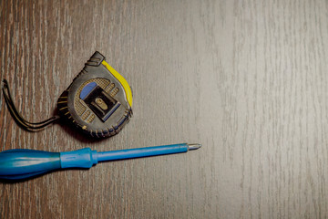 screwdriver and measuring tape on wooden background
