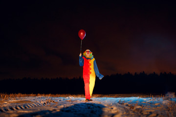 Full-length image of clown with colorful balloons at night