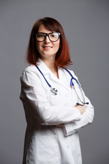 Picture of smiling female doctor in white coat and with phonendoscope in glasses